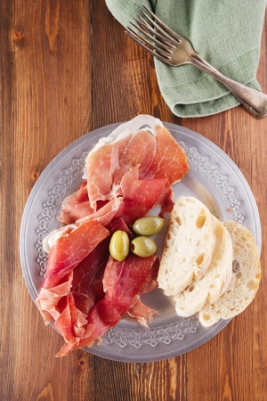 Platter of serrano jamon Cured Meat, Ciabatta, chorizo and olives photo