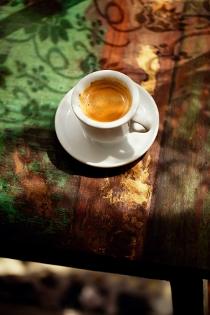 espresso coffee cup on rustic table with sun