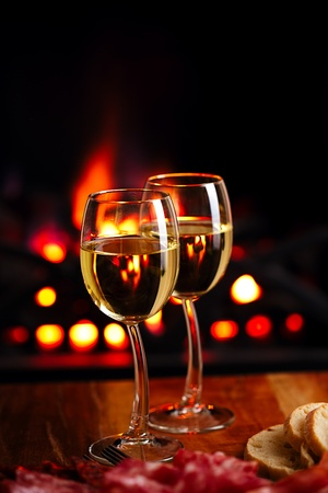 two white wine glasses  with cozy fireplace  background photo