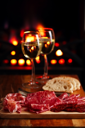 cured: Platter of serrano jamon Cured Meat with cozy fireplace and wine background Stock Photo