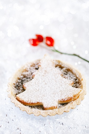 powdered sugar: christmas  tart with marzipan tree on white snow festive background