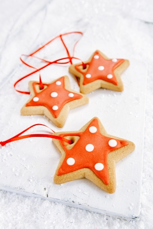 Gingerbread star cookies on  on white wood and festive Christmas snow background, nice postcard Stock Photo - 21129740