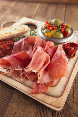 Platter of serrano jamon Cured Meat, Ciabatta, chorizo and olives photo