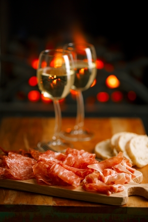 Platter of serrano jamon Cured Meat with cozy fireplace and wine background Stockfoto