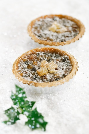 mincemeat: christmas  tart with mincemeat and candied peel on white snow festive background Stock Photo