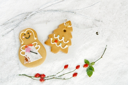 Gingerbread tree cookies and girl on  on white wood and festive Christmas snow background, nice postcard photo