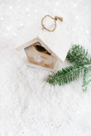 wooden bird house christmas decoration on white snow background photo