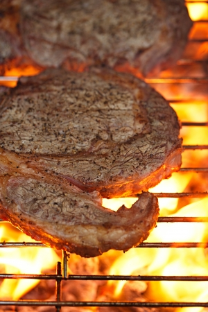 food meat -  rib eye beef steak on party summer barbecue grill with flame. Shallow dof. photo