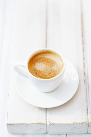 espresso coffee in white cup on old rustic  style table, shallow dof photo