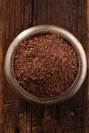 fine grated chocolate in bowl on wood , shallow dof photo