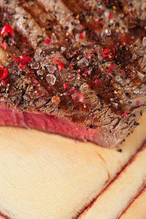 Beef steak on a wooden board and table photo