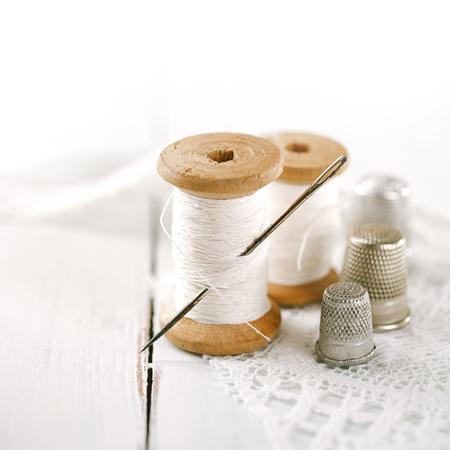 hilo rojo: reales viejos carretes cucharas pisa con aguja y dedal en la mesa de madera blanca