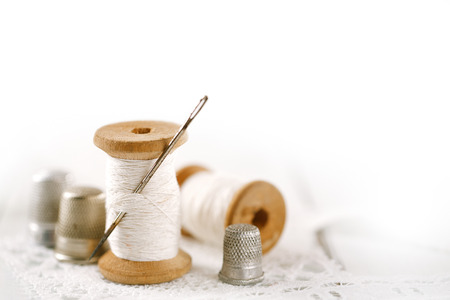 needle lace: real old reels spoons treads with needle and thimble on white wooden table