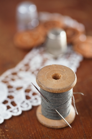 old spools: real old reels spoons treads with needle and thimble on old wooden table Stock Photo