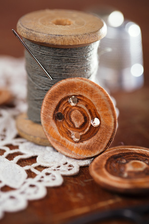 needle lace: real old reels spoons treads with needle and thimble on old wooden table Stock Photo