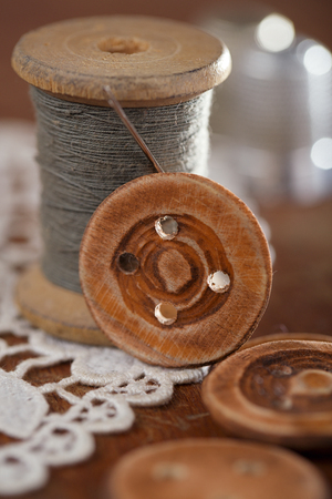 thimble: real old reels spoons treads with needle and thimble on old wooden table Stock Photo