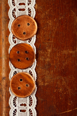 bottons: three handmade wooden bottons on old table and lace Stock Photo