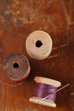 needle lace: real old reels spoons treads with needle  on old wooden table Stock Photo