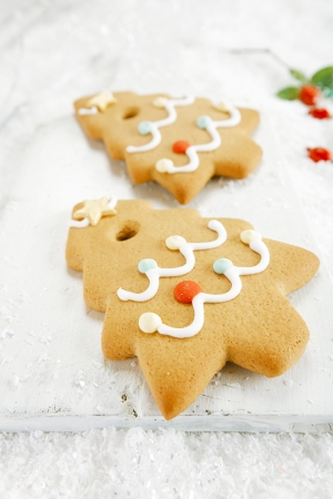 Gingerbread tree cookies on  on white wood and festive Christmas snow  photo