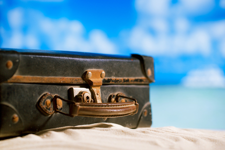 old retro antique suitcase on beach, sea and sky backgound photo