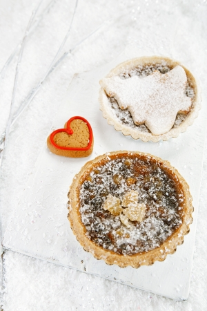 mincemeat: christmas  tart with mincemeat and tart with marzipan tree  on white snow festive  Stock Photo