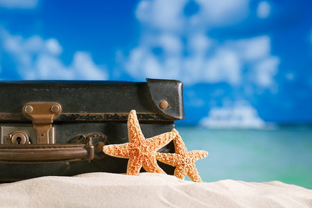 antique suitcase: old retro antique suitcase on beach with starfish, ocean and sky backgound Stock Photo