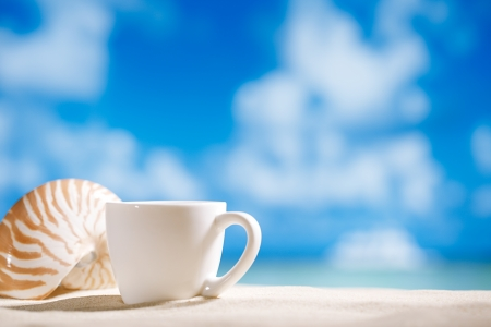 dof: white espresso coffee cup with ocean , seashell, beach and seascape. Shallow dof. Stock Photo