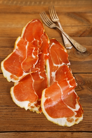cured ham: serrano ham jamon Cured Meat on wooden table