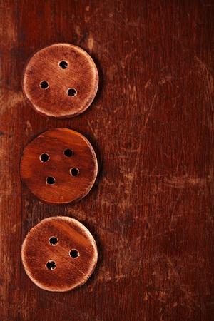 bottons: three handmade wooden bottons on old table