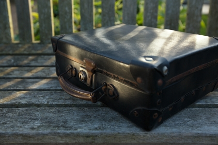 travelled: old black suitcase on wooden bench … shallow dof