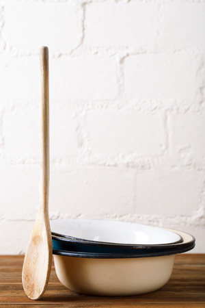 kitchen tools: retro kitchen utensils  wood spoon and old enamel bowls in rustic style