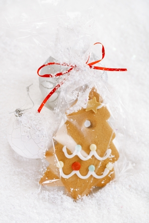 Gingerbread tree cookie in a bag on white  snow background, nice postcard photo