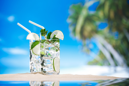 mojito cocktail with ice, rum, lime and mint   in a  glass  on beach sand and  blue stars background photo