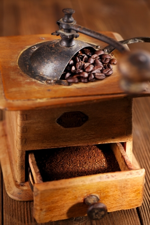 Whole and ground coffee beans from a hand coffee grinder photo