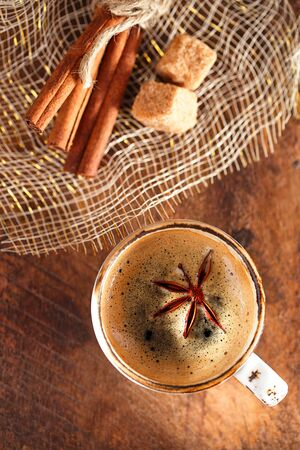 anis: A cup of spiced coffee with anis star and cinamon sticks and sugar