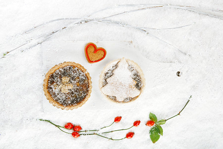 mincemeat: christmas  tart with mincemeat and tart with marzipan tree  on white snow festive background