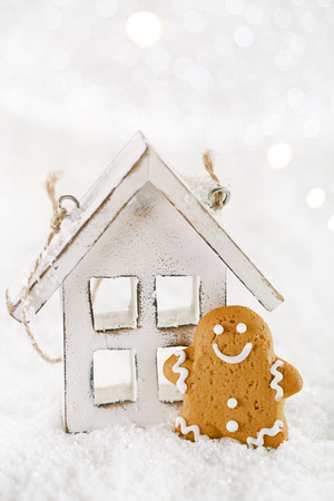 Gingerbread man and wooden house on a festive Christmas snow background, nice postcard photo