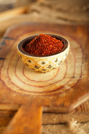 pepper flakes: red hot chillies pepper  flakes in bowl on wooden board