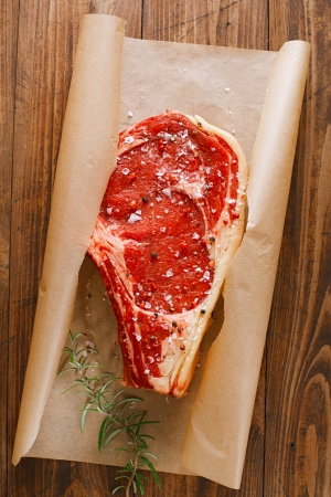 raw beef Rib steak with bone on wooden board and table photo
