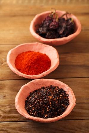 chiles secos: chipotle - jalapeños ahumados hojuelas de chile, planta y todo en cuencos de cerámica, dof bajo Foto de archivo