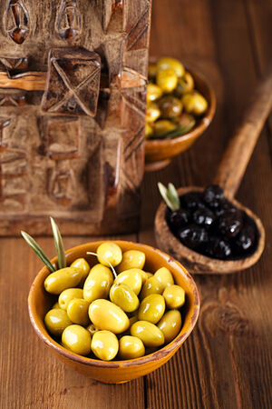 moroccan cuisine: marinated Olives in bowls with moroccan  ornament on wood, shallow dof