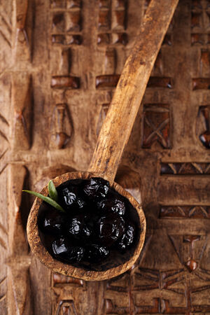 marinated Olives in old spoon with moroccan  ornament on wood, shallow dof photo