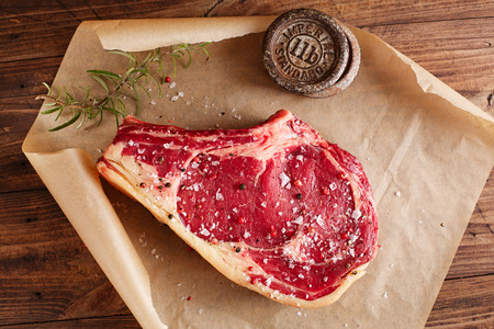 raw beef Rib bone  steak  on paper  and table with 2lb iron weight
