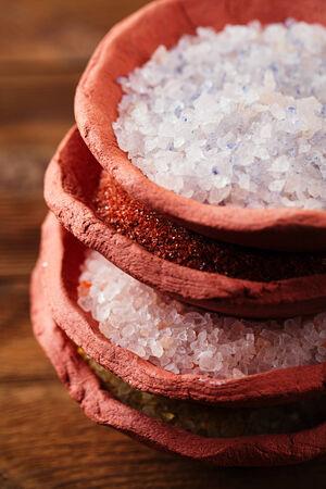 different type of salt in rustic clay bowls stacked, Himalayan Pink Crystal Rock salt,Hawaiian Red Alaea Sea Salt,Persian Blue Iranian,Lemon Salt Stock Photo