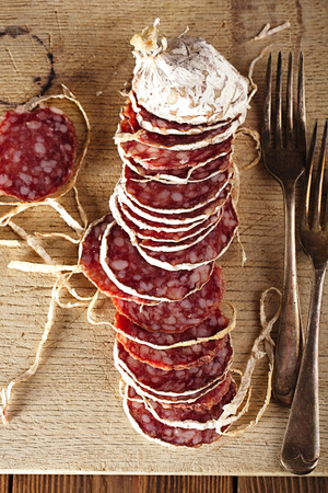 italian salami: Dried french sausages salami on wooden platter, rustic style