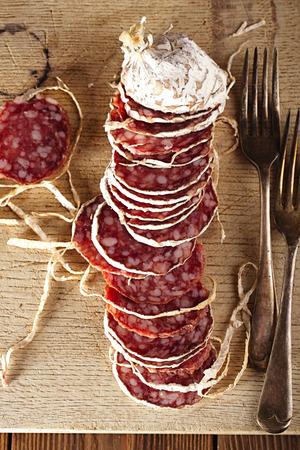 salami: Salchichas fritas secas salami en un plato de madera, estilo rústico Foto de archivo