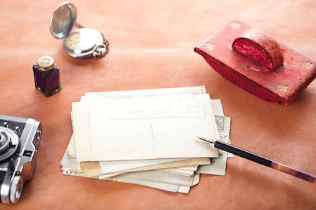 retro photo post cards , vintage ink , pen, blotter and camera on old leather table photo