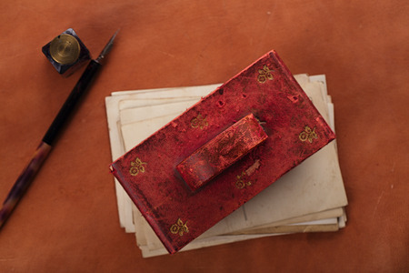 fray: vintage red leather ink blotter  with retro post cards on leather table, shallow dof Stock Photo
