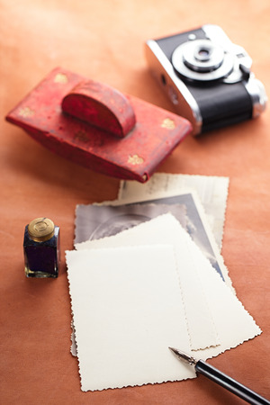 blotter: retro photos , vintage ink , pen, blotter and camera on old leather table Stock Photo