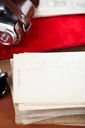 fray: pile of vintage post cards with  ink pen, inkpot on leather table, retro colors